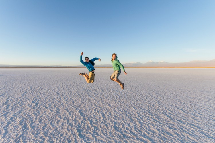 Two male friends jumping on salt flat desert landscape while adv