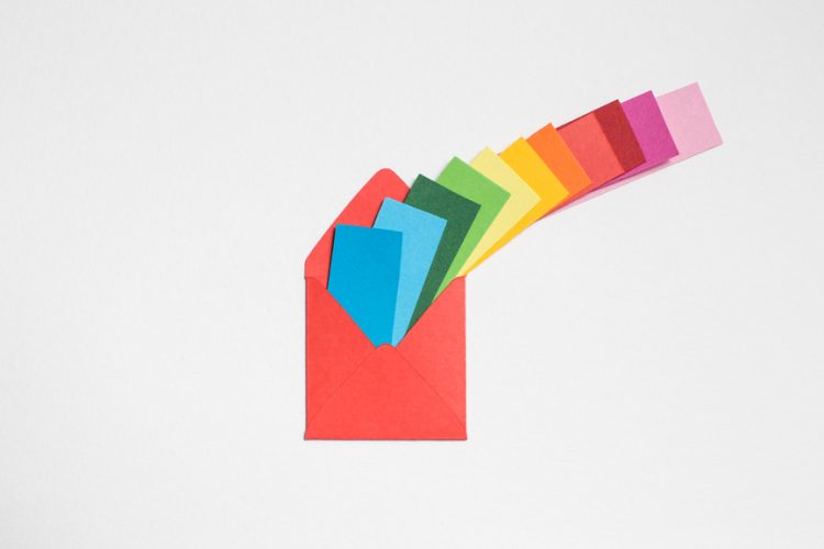 A paper envelope with multi-coloured cards flying outwards
