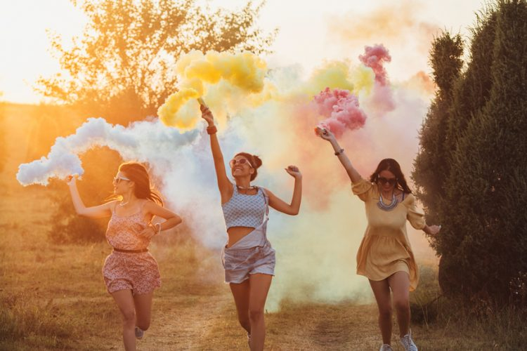 Three happy girls holding smoke bombs in different colours and running.