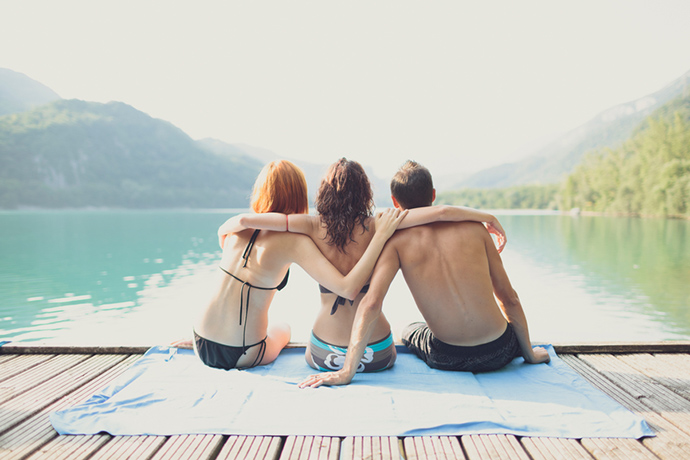 Three friends sit on a jetty by a lake