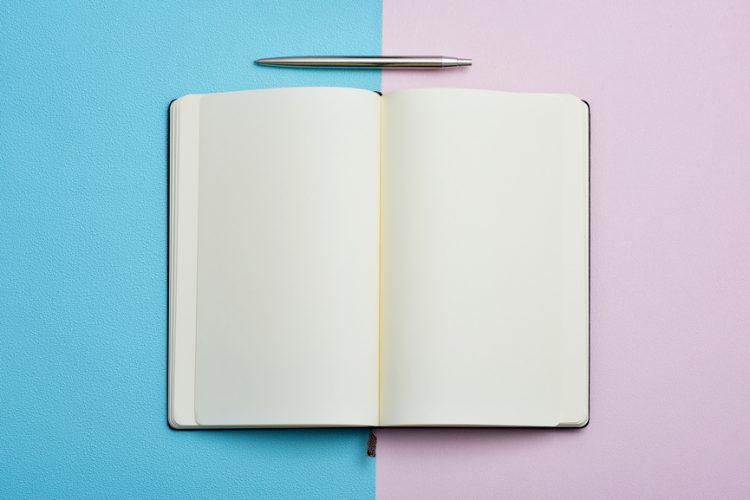 notepad opened and pen on a blue and pink background