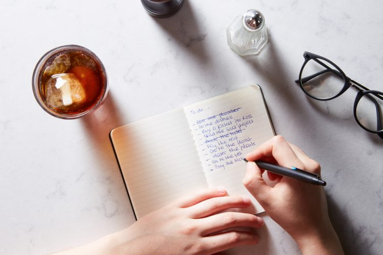 Above view of person writing to do list in notebook at table with glasses and iced coffee