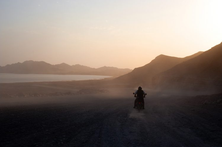 Person riding a motorbike through picturesque scenery