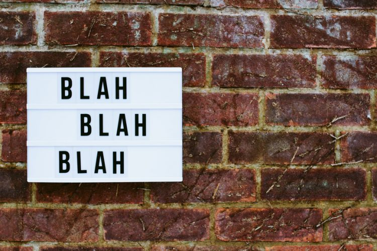 "Sign on a wall reading ""blah blah blah"""