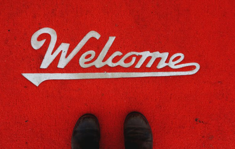 A red welcome mat and a pair of black shoes upon it