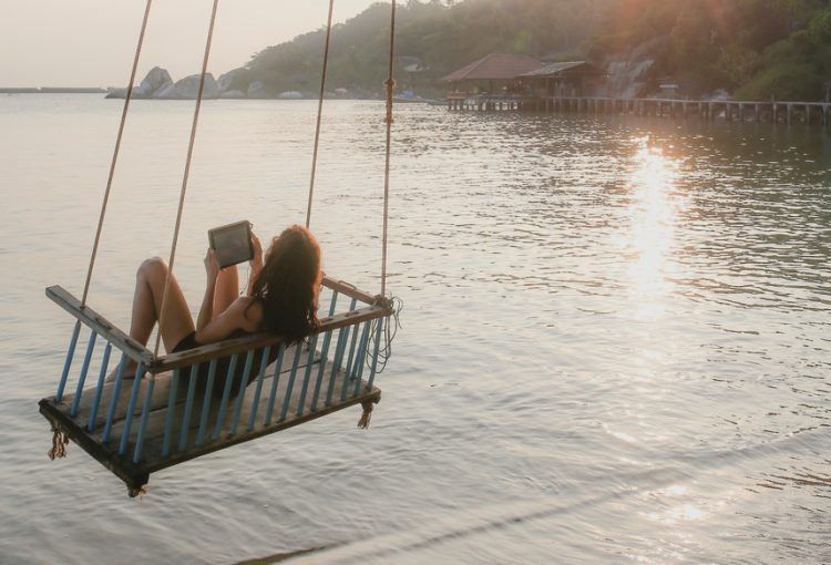 Young girl using tablet computer in seated rope swing over the ocean water on tropical island at sunset.