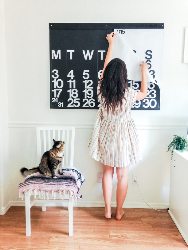Woman adjusting wall calendar