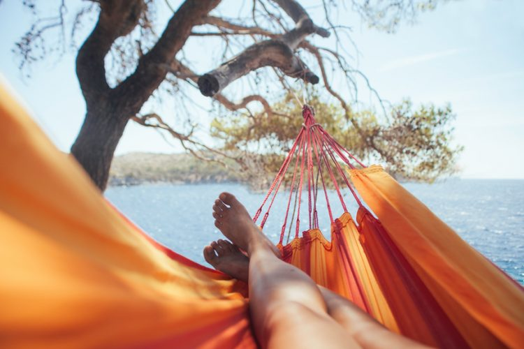 Woman's legs on a bright orange hammock near the sea
