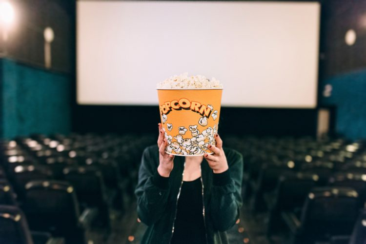 Woman holding popcorn bucket over her face in a cinema
