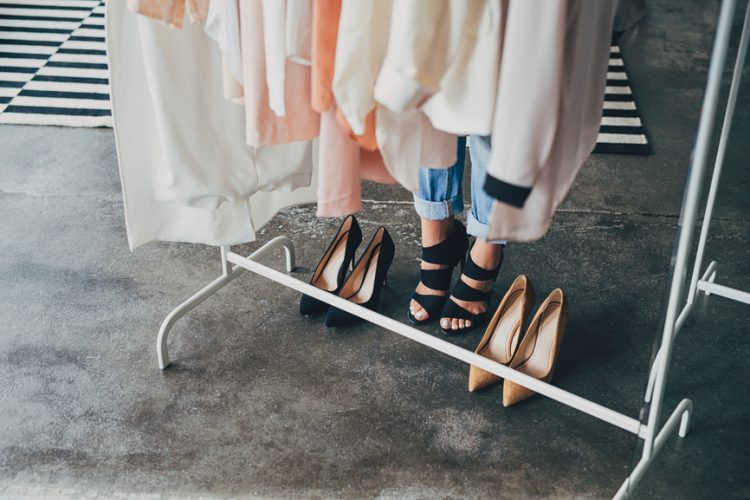 Unrecognisable woman wearing heels standing by the clothes rack.