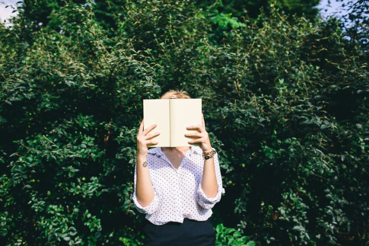 Woman holding a book in front of face with plants on the background