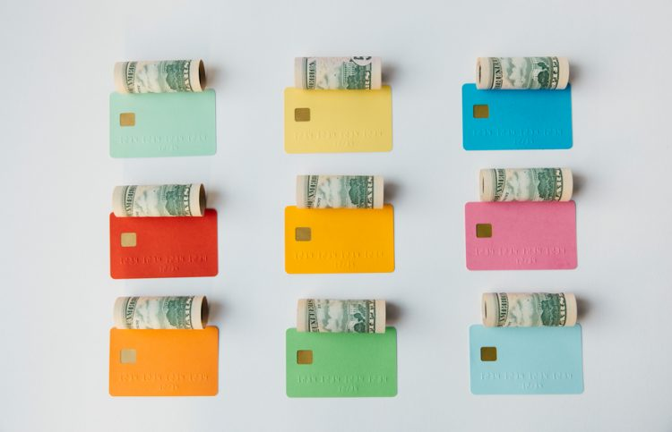 Coloured credit cards and cash notes protruding from them