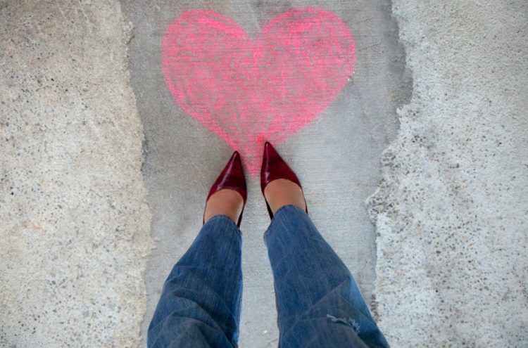 Love heart on a sidewalk and the legs of a woman