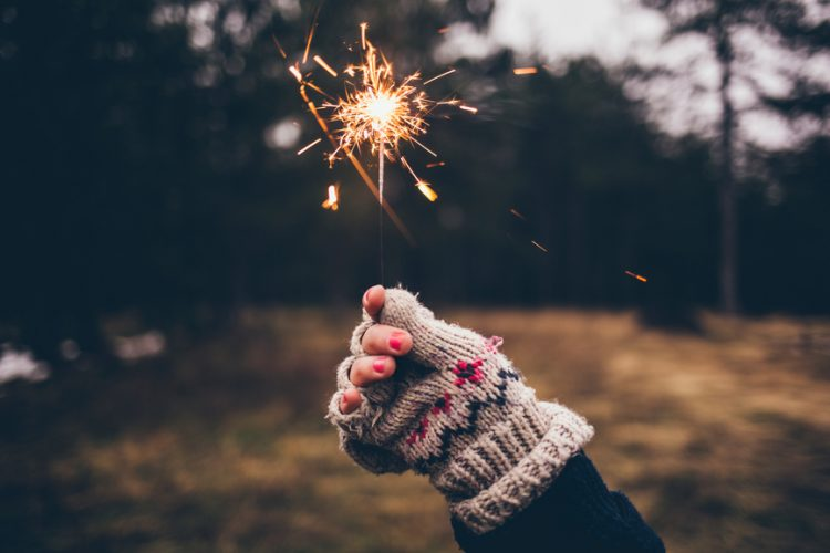A gloved hand holding up a sparkler