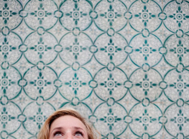 Woman looking upwards against a pretty tiled background