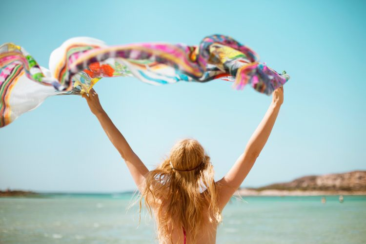 Woman waving a coloured scarf by the ocean