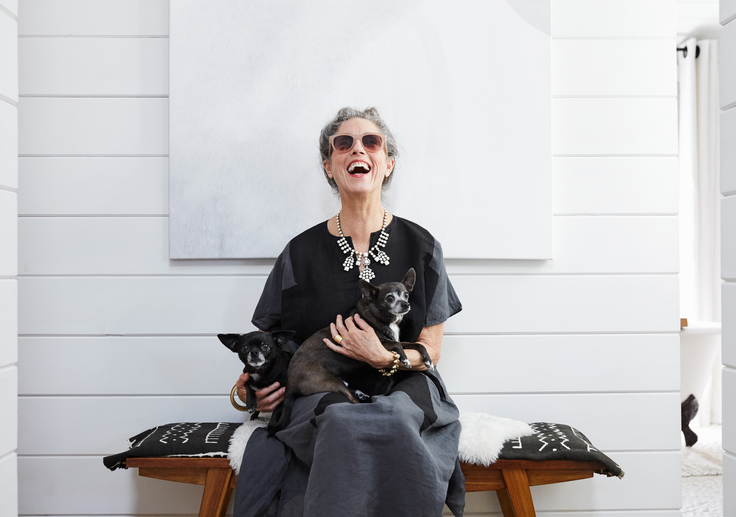 Older woman laughing with puppies in her lap