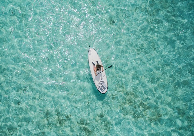 Woman paddleboarding on a blue sea