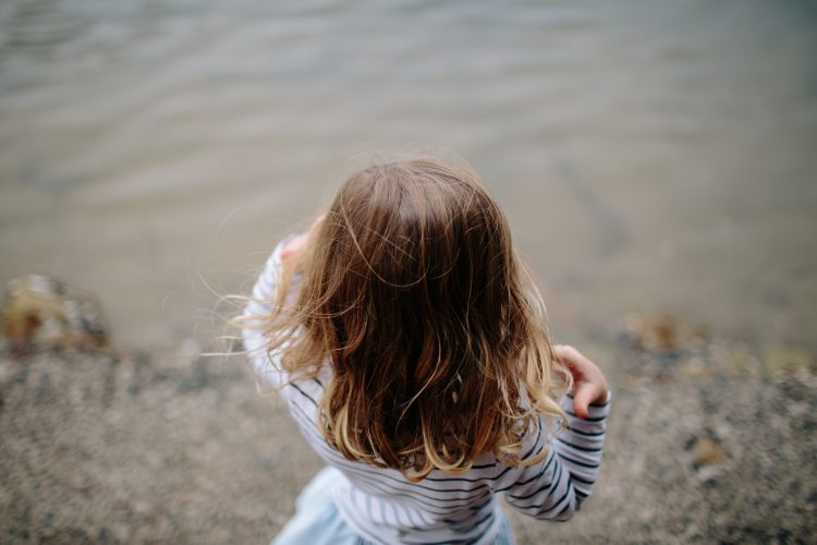 A young girl photographed by a lake