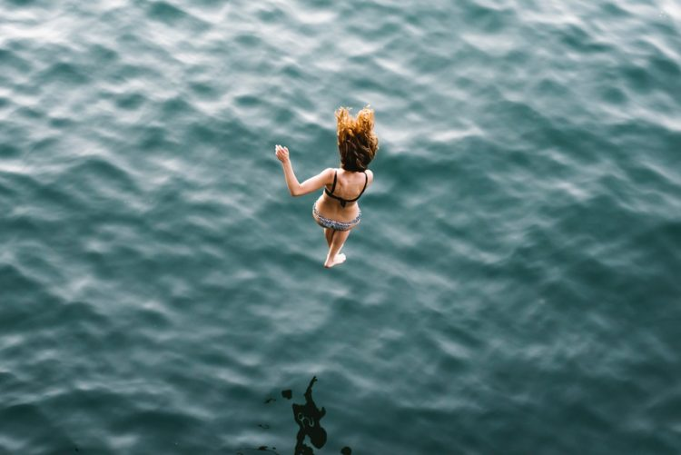 Woman jumping into the ocean from high up