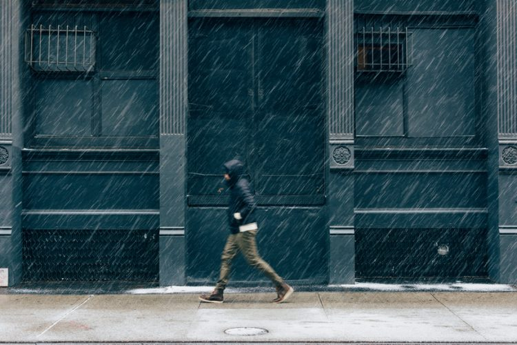 Man walking down a city street in the rain