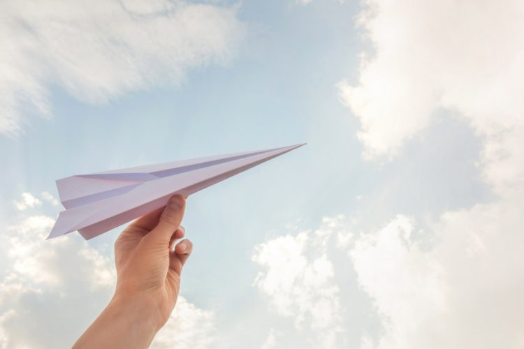 A hand holding a paper plane poised to the sky