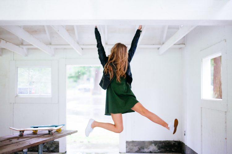 Girl jumping for joy in a green dress