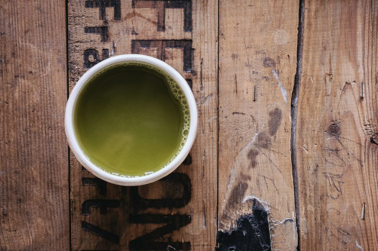Cup of green tea on a wooden table