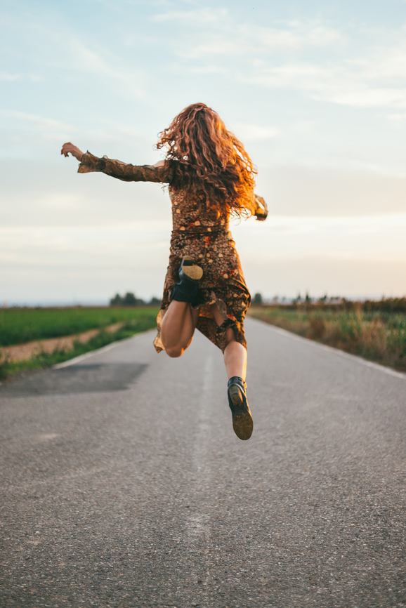 Woman jumping on an empty road