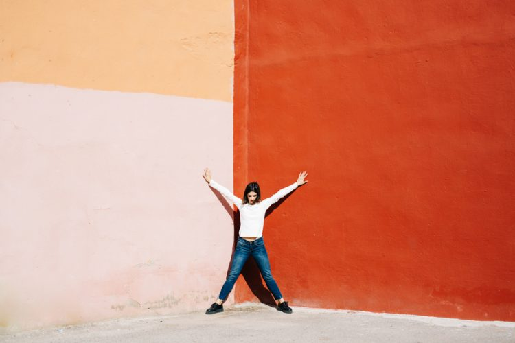 """Woman in casual outfit standing in """"star"""" pose in corner of two colorful walls in sunlight."""