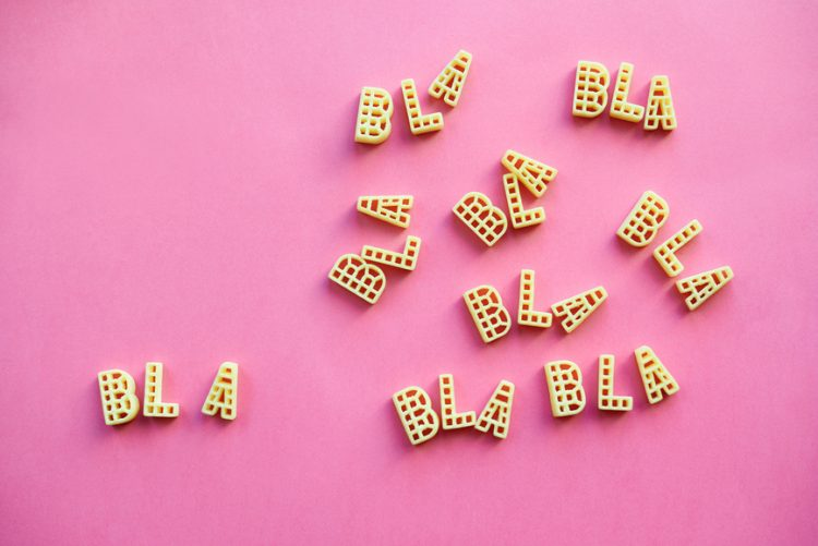 Alphabet pasta forming multiple words 'bla' lying on pink paper background.