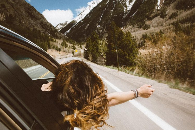 Woman leaning out the window of a moving car