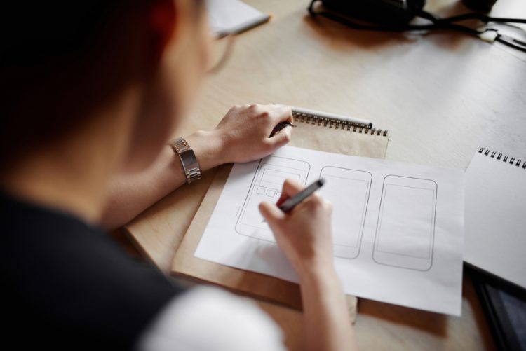 Close-up view of unrecognizable designer sitting at table and drawing sketches of new mobile phone