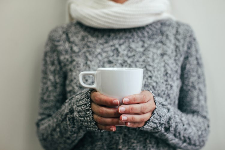 Woman in woollen jumper and scarf, holding a cup of tea