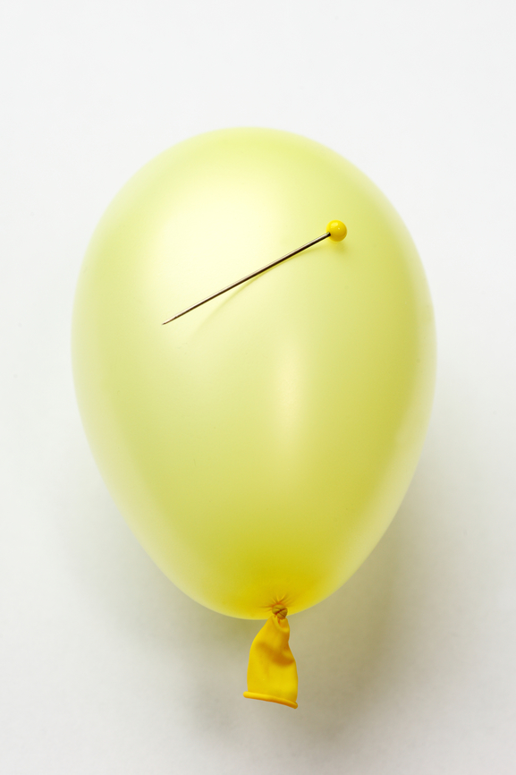 Pale yellow balloon with a pin resting on top
