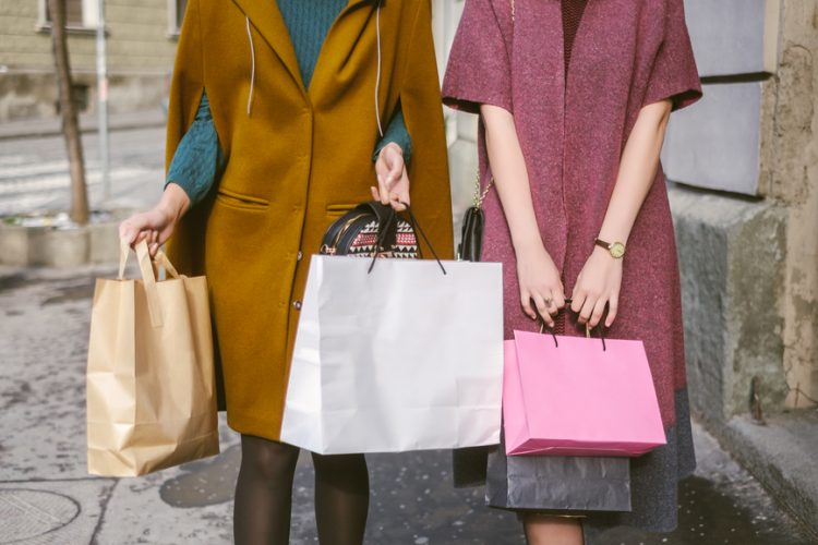 Two women in bright coats holding numerous shopping bags