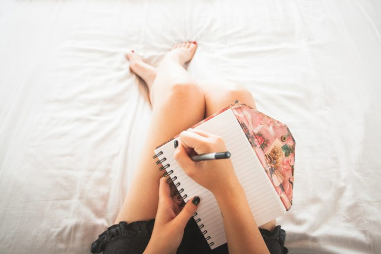 Women sitting in bed with white sheets writing in a notebook.