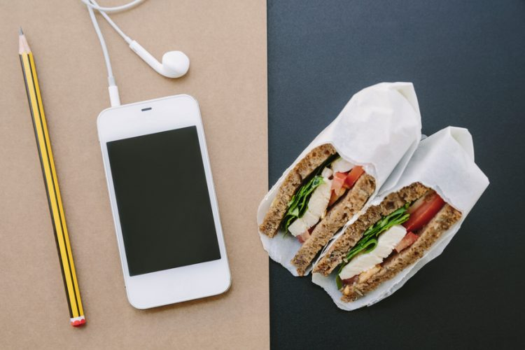 A sandwich and some healthy snacks next to a note pad and a smart phone