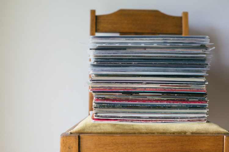 A stack of records piled on a chair