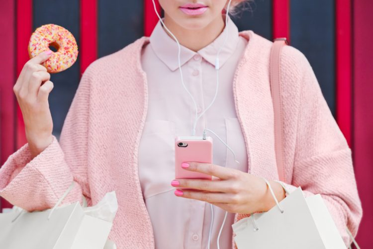 Pink Shopping Lady with doughnut using technology