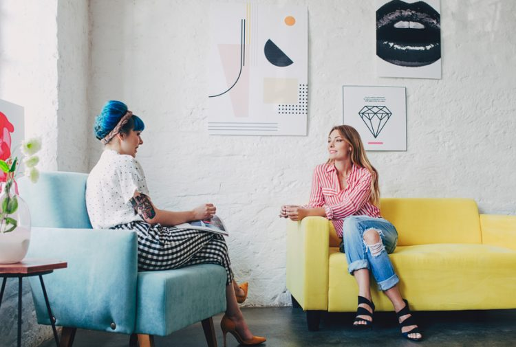 Two young stylish women sitting and talking