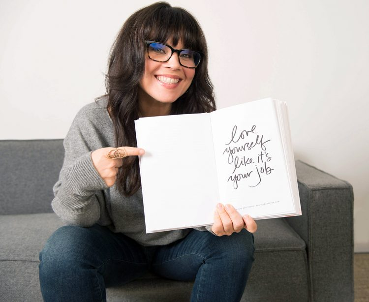 "Danielle LaPorte holding a page open that reads, ""Love yourself like it's your job"""
