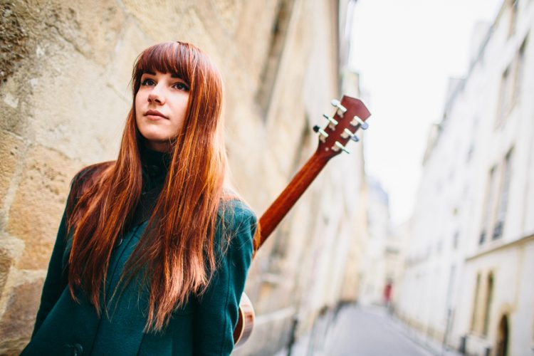 Young cute woman walking on the street with her guitar