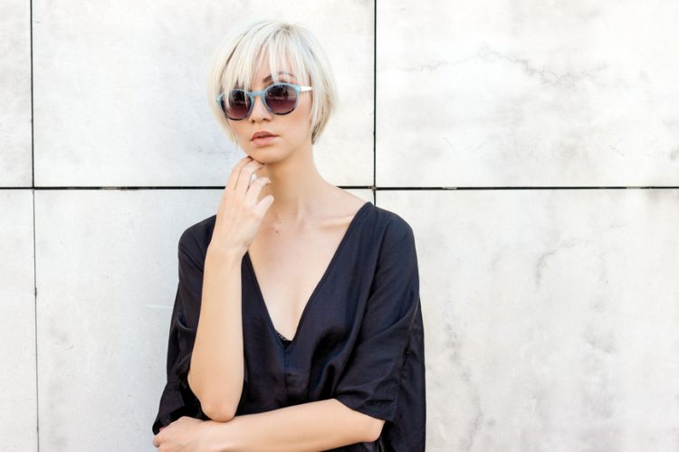 Woman in sunglasses posing by a white wall