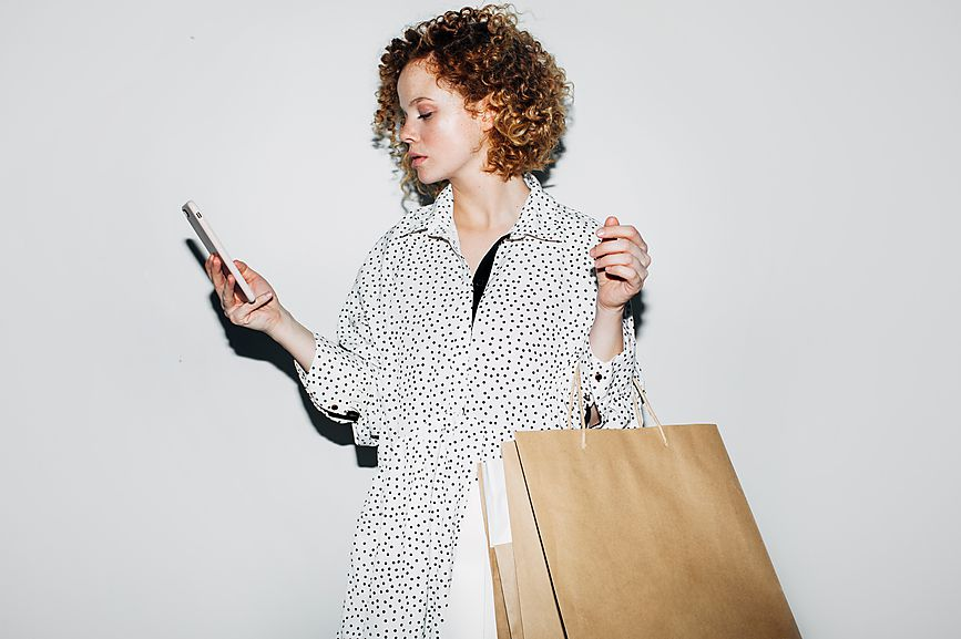 Woman with shopping bags on her phone