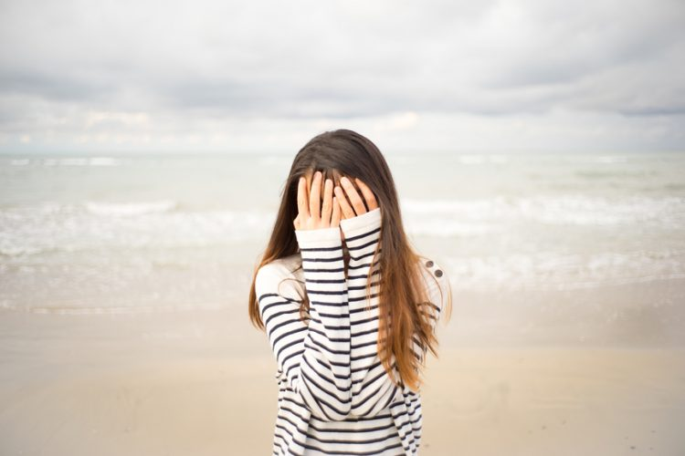 Woman on beach holding her hands to her face