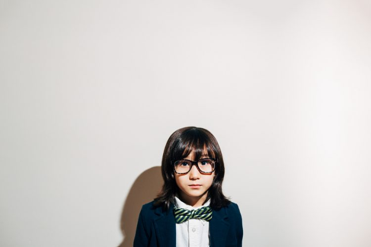young mixed race child in bow tie and glasses looks seriously at camera