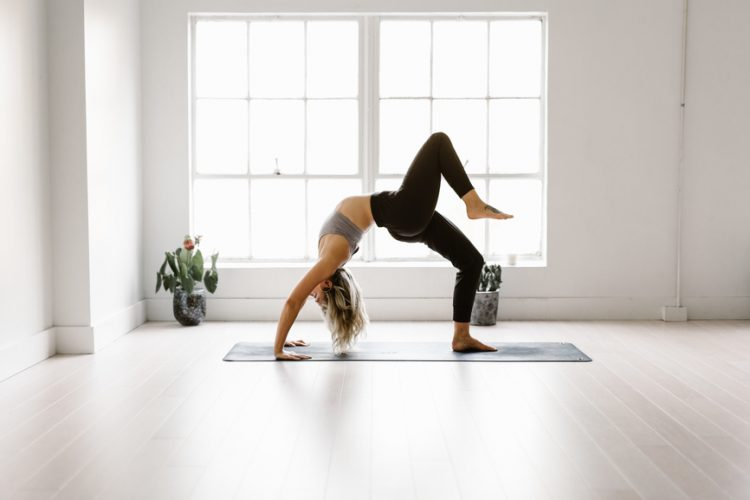 Blonde woman practices yoga in white backlit studio.