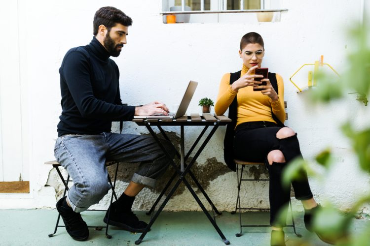 Full length of handsome businessman working on laptop at table beside stylish woman using mobile phone. Lunch break outdoors.