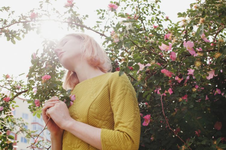 Portrait of cute blonde female with short hair wearing yellow dress near pink blossom briar